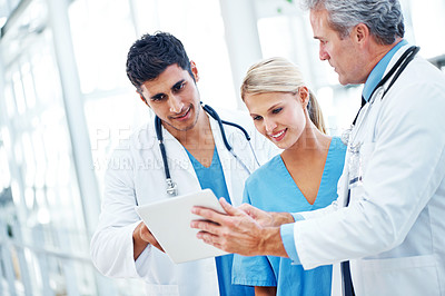 Buy stock photo Three doctors working together on a digital tablet