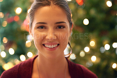 Buy stock photo Portrait of a beautiful young woman in front of a christmas tree