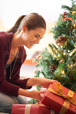 Buy stock photo Shot of an attractive young woman looking through presents under a christmas tree