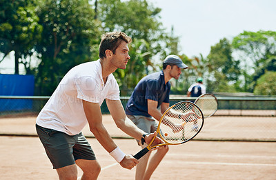 Buy stock photo Shot of two tennis players on the same team waiting for the ball
