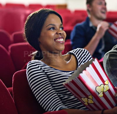 Buy stock photo Shot of a woman laughing while watching a movie at the cinema