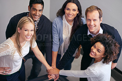 Buy stock photo Shot of a group of businesspeople in a huddle with their hands together