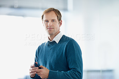 Buy stock photo Shot of a young businessman sending a text message while standing in an office