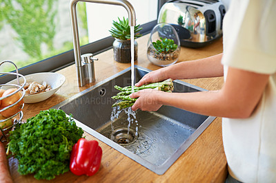 Buy stock photo Cropped shot of a woman washing vegetables in a kitchen sink