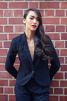 Buy stock photo Shot of a beautiful woman wearing a classic feminine suit leaning against a brick wall