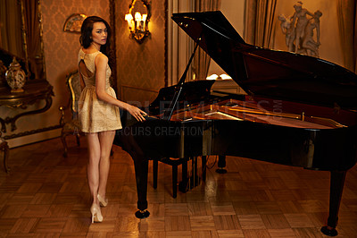 Buy stock photo Portrait of a beautiful young woman standing beside a piano