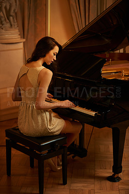 Buy stock photo Rearview shot of a stylish young woman playing the piano