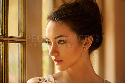 Buy stock photo Cropped shot of a beautiful young woman standing by a window