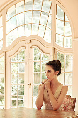 Buy stock photo Shot of a beautiful young woman sitting at a table in her elegant home
