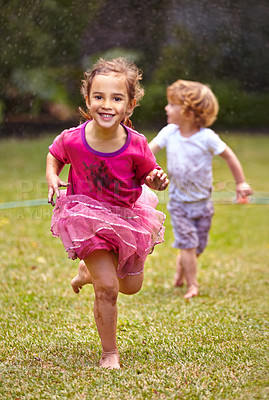 Buy stock photo Shot of a little girl running with her little brother outside