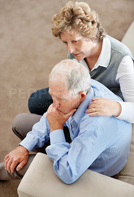 Buy stock photo A senior woman comforting her husband while sitting on a sofa