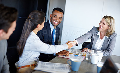 Buy stock photo Shot of professional coworkers shaking hands during a meeting in the office