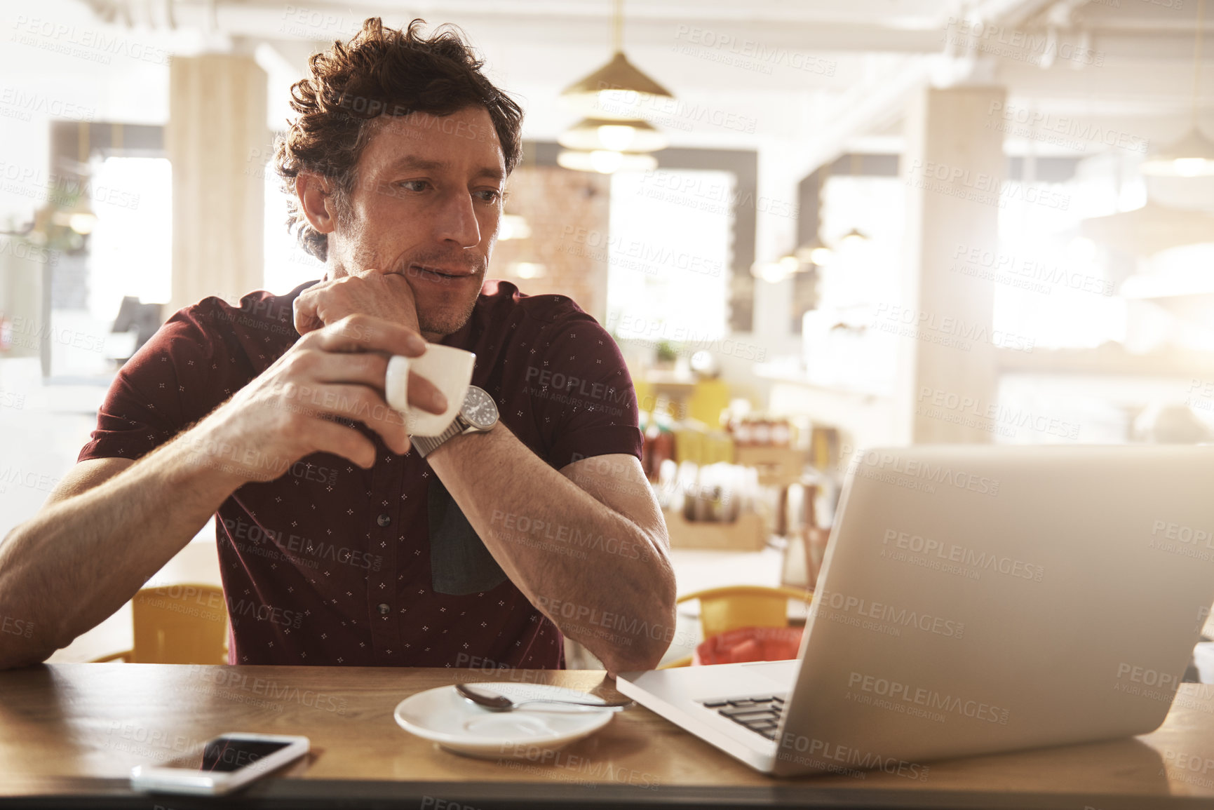 Buy stock photo Shot of a man having coffee while sitting with his laptop in a cafe