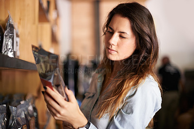 Buy stock photo Shot of a beautiful woman in a store looking carefully at a packet of coffee beans