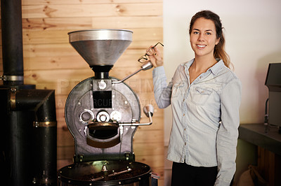 Buy stock photo Portrait of a young woman working an old-fashioned coffee bean roasting machine
