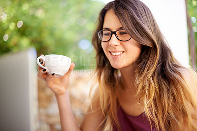 Buy stock photo Shot of a smiling young woman looking at her laptop screen outside with a cup of coffee