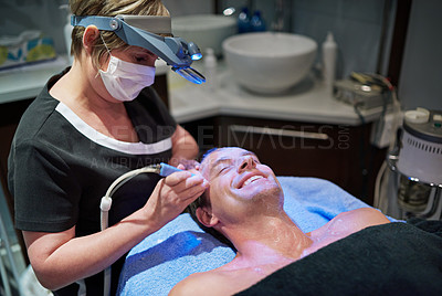 Buy stock photo Shot of a man getting a non-invasive face lift at a beauty clinic
