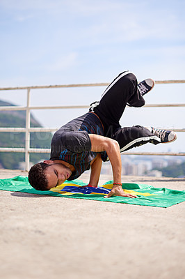 Buy stock photo Low angle shot of a young male breakdancer in an urban setting