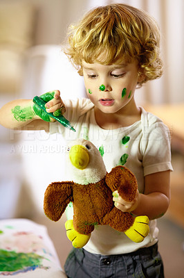 Buy stock photo Shot of an adorable little boy making a mess while painting