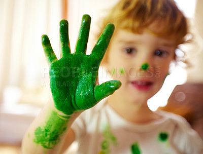 Buy stock photo Portrait of a messy child displaying their painted hand