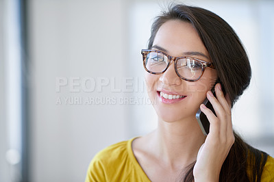 Buy stock photo Shot of an attractive young woman talking on a cellphone in an office