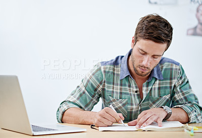 Buy stock photo Shot of a casually-dressed young man using a digital tablet at his desk. The commercial designs displayed in this image represent a simulation of a real product and have been changed or altered enough by our team of retouching and design specialists so that they are free of any copyright infringements