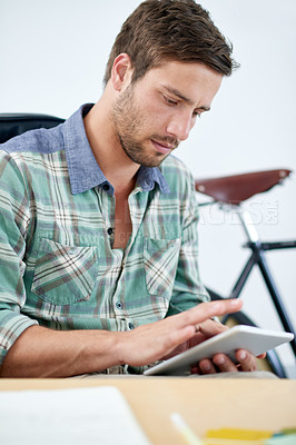 Buy stock photo Shot of a young designer sitting at his office desk