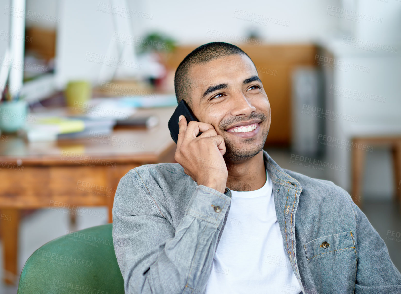 Buy stock photo Shot of a handsome young office worker talking on a cellphone while sitting in an office
