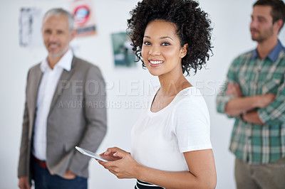 Buy stock photo Portrait of an attractive young businesswoman using a digital tablet with her colleagues in the background. The commercial designs displayed in this image represent a simulation of a real product and have been changed or altered enough by our team of retouching and design specialists so that they are free of any copyright infringements