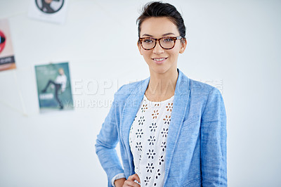 Buy stock photo Shot of a beautiful young woman working in a modern office. The commercial designs displayed in this image represent a simulation of a real product and have been changed or altered enough by our team of retouching and design specialists so that they are free of any copyright infringements