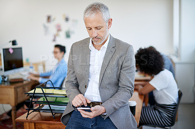 Buy stock photo Shot of a mature businessman using a cellphone while sitting on a table in an office