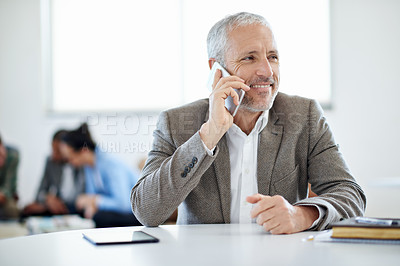 Buy stock photo Shot of a mature businessman talking on a cellphone while sitting at a table in an office