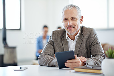 Buy stock photo Portrait of a mature businessman using a digital tablet while sitting at a table in an office