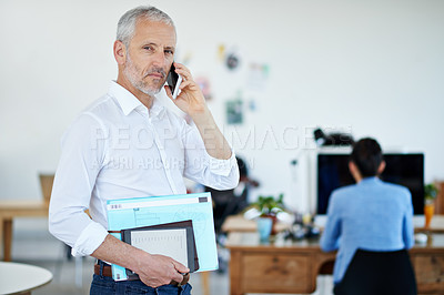 Buy stock photo Shot of a mature businessman talking on a cellphone while standing in an office