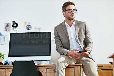 Buy stock photo Shot of a casually-dressed young man sending a text message while at work. The commercial designs displayed in this image represent a simulation of a real product and have been changed or altered enough by our team of retouching and design specialists so that they are free of any copyright infringements