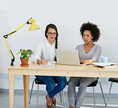 Buy stock photo Shot of two young businesswomen working on a laptop