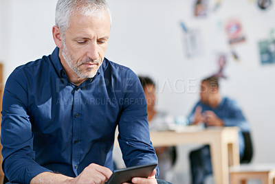 Buy stock photo Shot of a handsome businessman using a digital tablet in the office. The commercial designs displayed in this image represent a simulation of a real product and have been changed or altered enough by our team of retouching and design specialists so that they are free of any copyright infringements