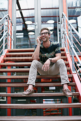 Buy stock photo Shot of a handsome young man using his mobile phone while sitting on the steps of an office