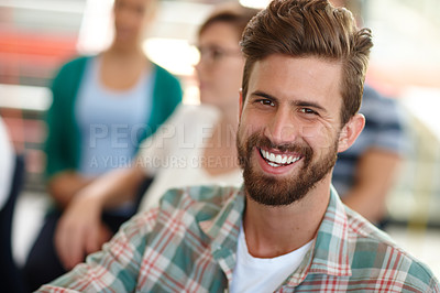 Buy stock photo Shot of a male designer smiling at the camera with his colleagues in the background