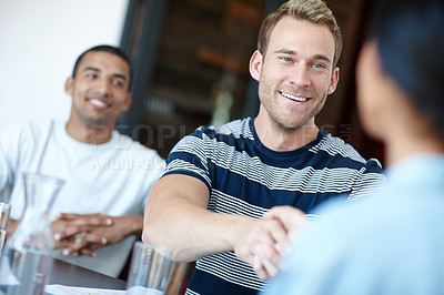 Buy stock photo Shot of a male designer shaking hands with a colleague during a meeting