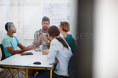 Buy stock photo Shot of a group of young designers discussing work in a meeting