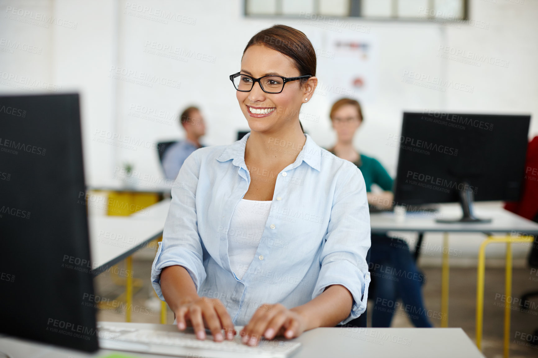 Buy stock photo Shot of a young female designer working on her office computer