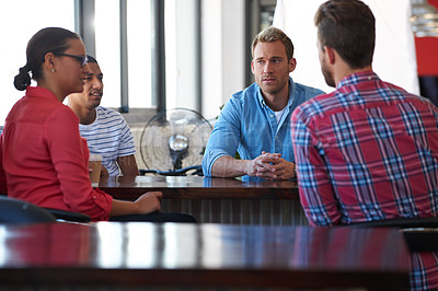 Buy stock photo Four coworkers sitting around a table and discussing some ideas