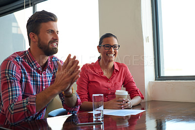 Buy stock photo Cropped shot of two young coworkers addressing someone out of shot