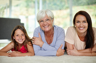 Buy stock photo Portrait of little girl lying on the carpet with her mother and grandmother