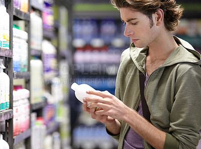 Buy stock photo A young man checking a certain product