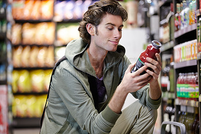 Buy stock photo A young man looking at the label on a product