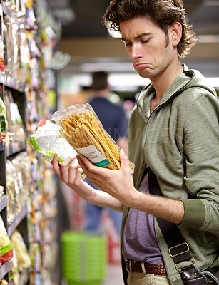 Buy stock photo A young man with two products in his hands in a grocery store