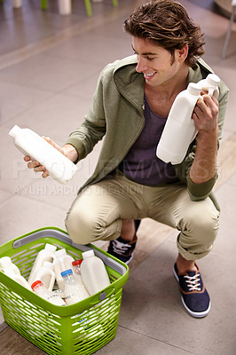 Buy stock photo A young man looking at the expiry date on a product