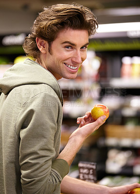 Buy stock photo A young man at the store buying fruit